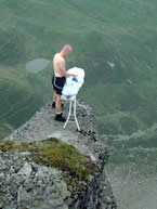 man using an ironing board on a high cliff edge