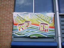 painted banner of houses floating away on a flood reading 'unforgotten'
