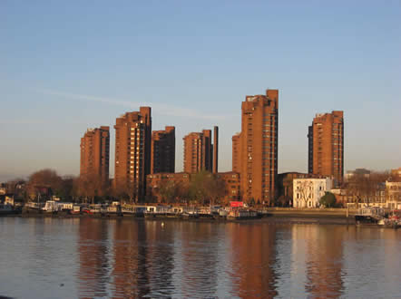 very tall rust coloured tower blocks reflected in the Thames